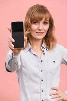 Portret dziewczyny z telefonem w dłoniach, piękna blondynka na różowym tle, trzyma telefon w dłoniach i pokazuje na nim, copyspace, różowe tło.