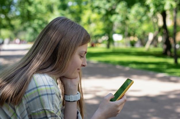Portret dziewczyny ze smartfonem w dłoniach na ławce w parku koncepcja ludzie i gadżety