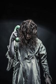 Portret dziewczyny zombie horror dzwoniąc przez telefon. straszny
