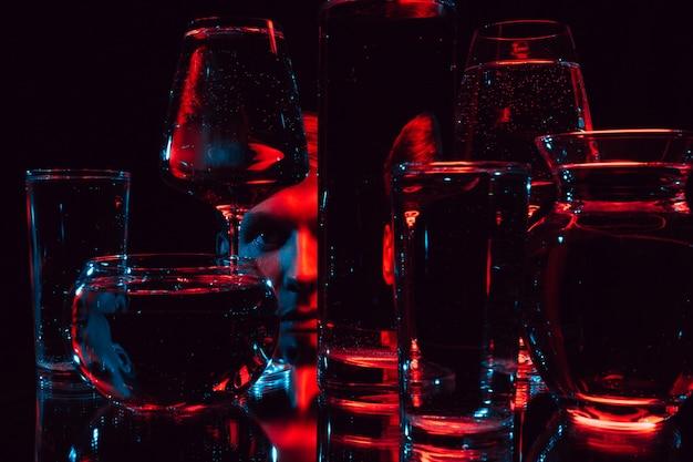 Portret dziwnego mężczyzny patrzącego przez szklane szklanki wody z odbiciami i zniekształceniami czerwonym, niebieskim światłem neonu