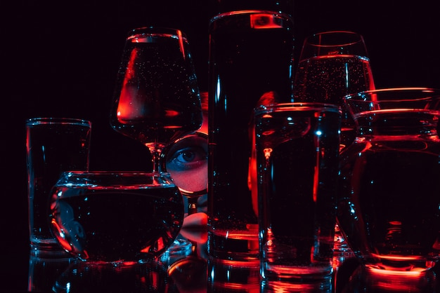 Portret dziwnego mężczyzny patrzącego przez szkło powiększające i szklane okulary z wodą z odbiciami i zniekształceniami