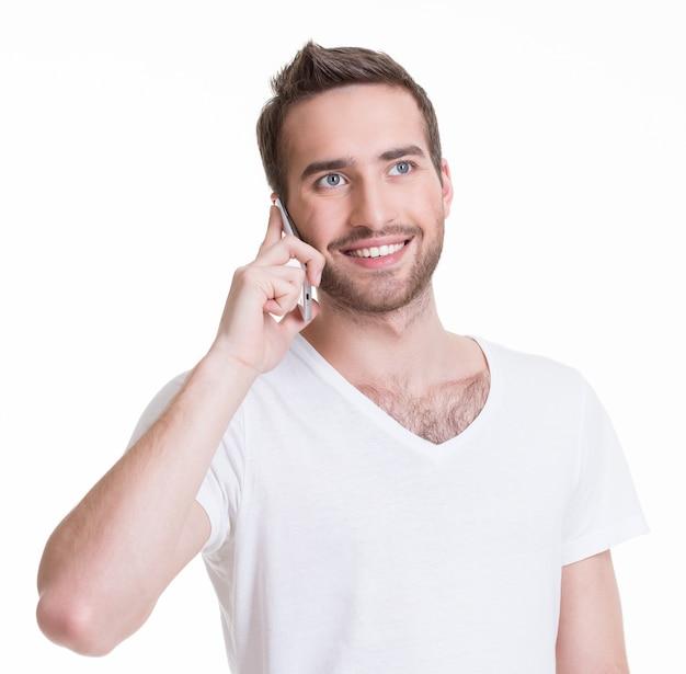 Portret dzwoni telefon komórkowy w przypadkowych szczęśliwy mężczyzna - na białym tle