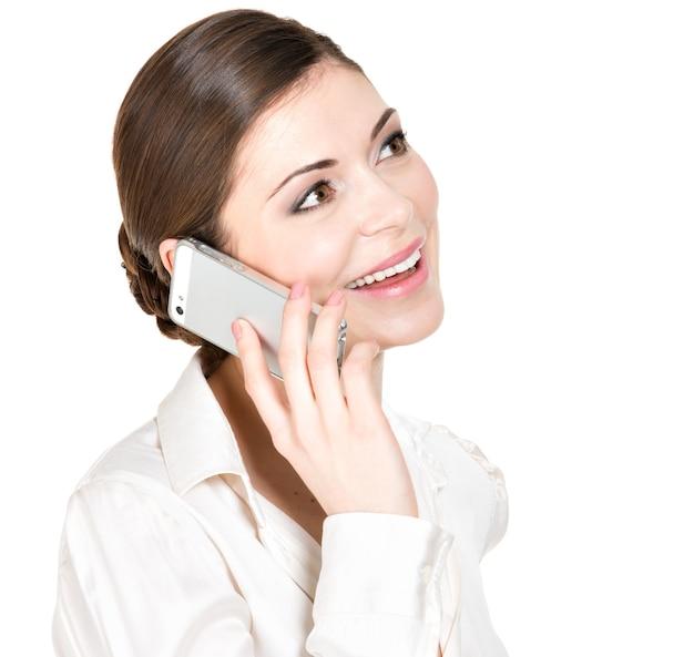 Portret dzwoniąc przez telefon komórkowy w białej koszuli szczęśliwa kobieta - na białym tle.