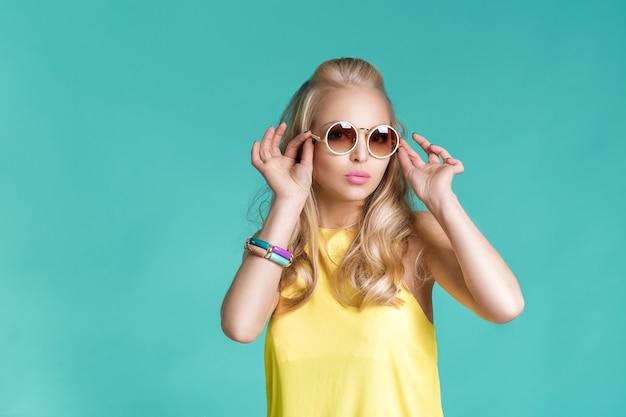 Portret efektowne piękne blond kobieta w okularach przeciwsłonecznych i żółtą koszulę na niebieskim tle. beztroskie lato.
