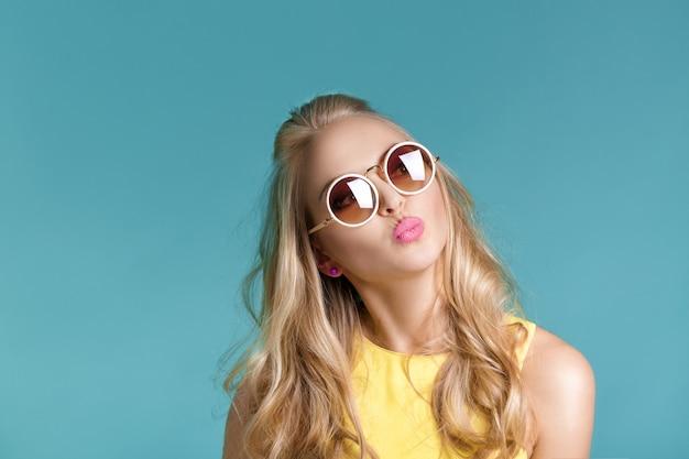 Portret efektowne piękne blond kobieta w okularach przeciwsłonecznych i żółtą koszulę na niebieskim tle. dziewczyna wysyła pocałunek w powietrzu