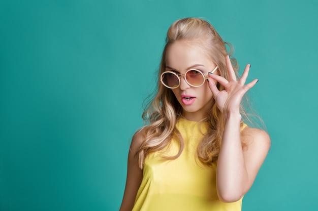 Portret efektowne piękne blond kobieta w okularach przeciwsłonecznych i żółtą koszulę na turkusowym tle. beztroskie lato.