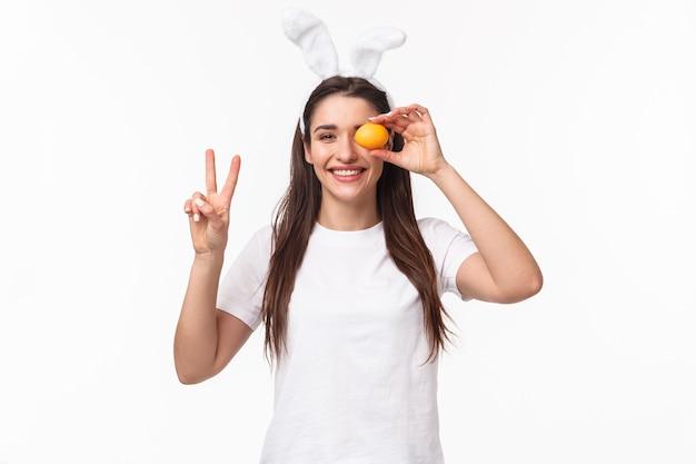 Portret ekspresyjna młoda kobieta nosi uszy i nos królika, trzymając kolorowe jajka