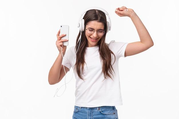 Portret ekspresyjna młoda kobieta z mobilną muzyką słuchania