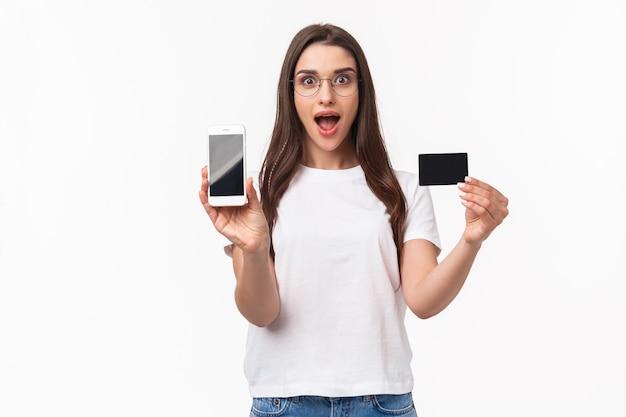 Portret ekspresyjna młoda kobieta z telefonem komórkowym i kartą kredytową