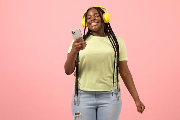 Portret ekspresyjnej afroamerykańskiej kobiety słuchającej muzyki