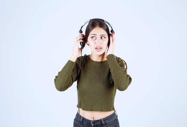 Portret ekspresyjnej młodej dziewczyny słuchającej muzyki z zaskoczonym wyrazem twarzy.