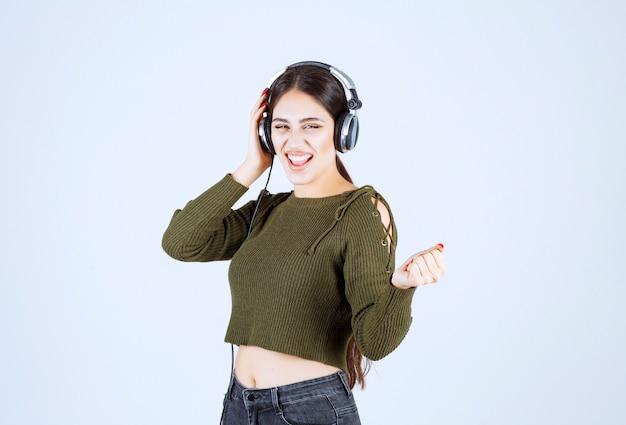 Portret ekspresyjnej młodej dziewczyny słuchania muzyki i tańca.