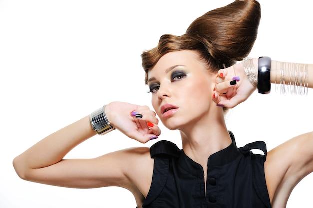 Portret ekspresyjnej pięknej dziewczyny z twórczej fryzury