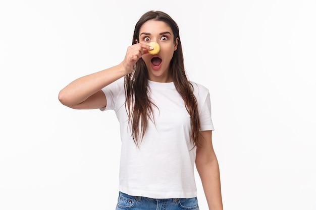 Portret ekspresyjny młoda kobieta trzyma smaczne dwa macarons na oczy