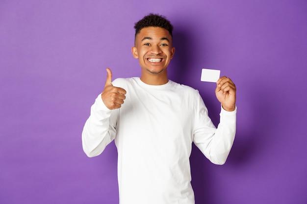 Portret ekspresyjny młody człowiek posiadający kartę kredytową