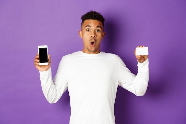 Portret ekspresyjny młody człowiek posiadający telefon i kartę kredytową