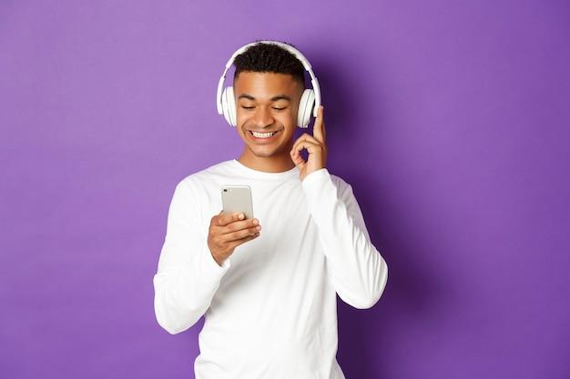 Portret ekspresyjny młody człowiek posiadający telefon komórkowy i słuchanie muzyki