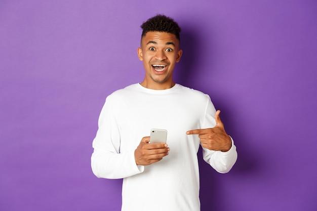 Portret ekspresyjny młody człowiek posiadający telefon komórkowy