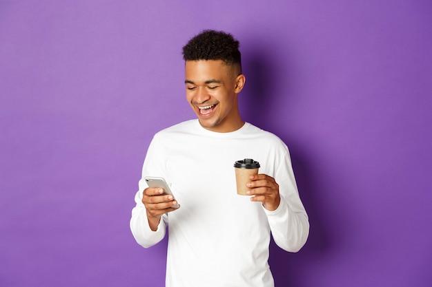 Portret ekspresyjny młody człowiek trzyma filiżankę kawy i mobile
