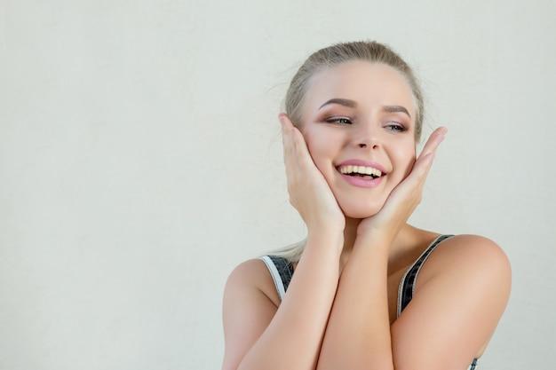 Portret ekspresyjny model blondynka z naturalnym makijażem pozowanie na białym tle. miejsce na tekst