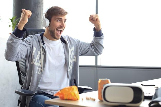Portret ekstatycznego faceta gracza w słuchawkach, krzycząc i radując się podczas grania w gry wideo na komputerze.