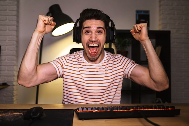 Portret ekstatycznego szczęśliwego młodzieńca 20s noszącego słuchawki, krzycząc, siedząc przy biurku w pokoju i grając w gry wideo