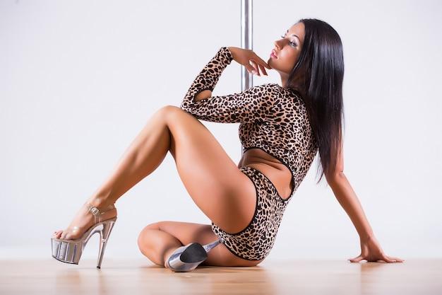 Portret elastycznej tancerki balansującej na słupie. na białym tle