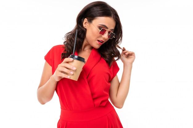 Portret elegancka brunetki dziewczyna w okularach przeciwsłonecznych i czerwonej sukni z szkłem na biel ścianie