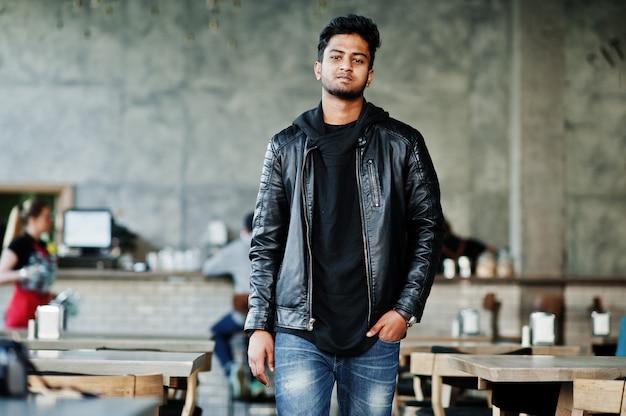 Portret elegancka i przypadkowa młoda azjatykcia mężczyzna odzież na skórzanej kurtce wydaje czas w kawiarni