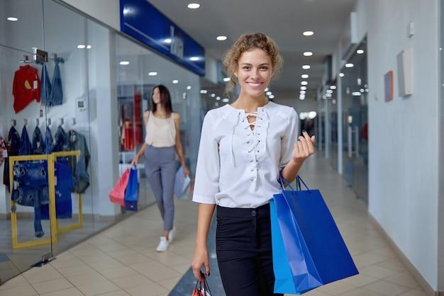 Portret elegancka kobieta robi zakupy w centrum handlowym z torbami
