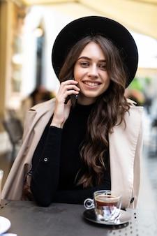 Portret elegancka kobieta w kapeluszu rozmawia na smartfonie, siedząc w przytulnej kawiarni