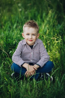 Portret elegancki blondynki chłopiec obsiadanie w parku wśród trawy