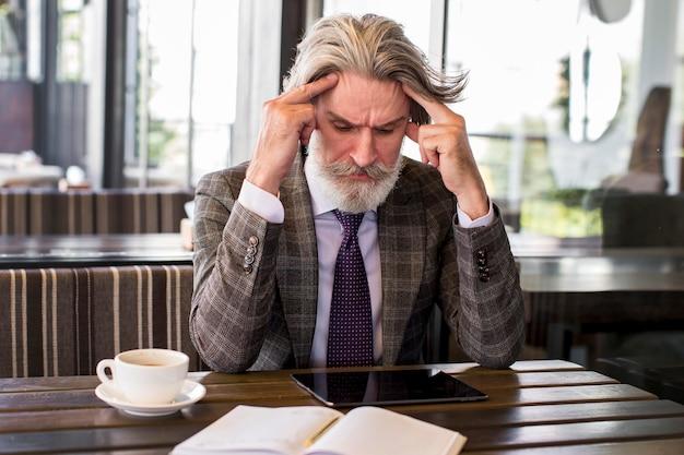 Portret elegancki dojrzały mężczyzna myśli w biurze