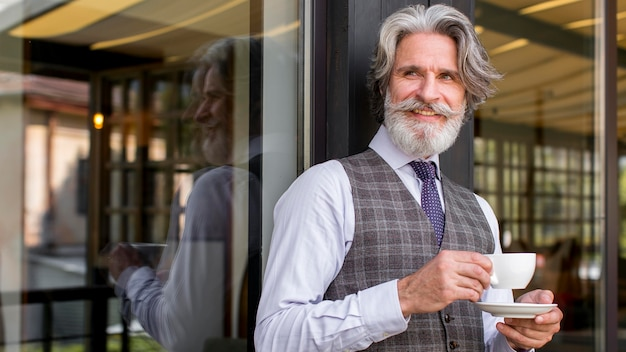 Portret elegancki dojrzały mężczyzna patrząc od hotelu