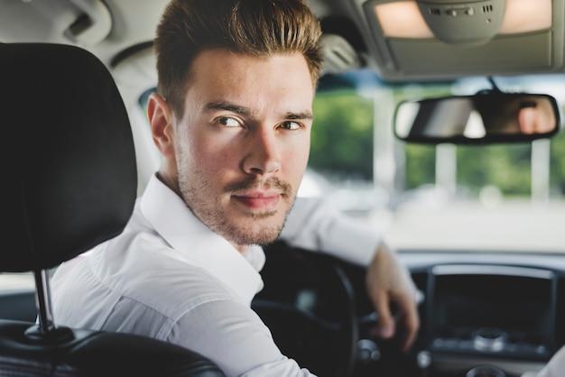 Portret elegancki młody człowiek w samochodzie