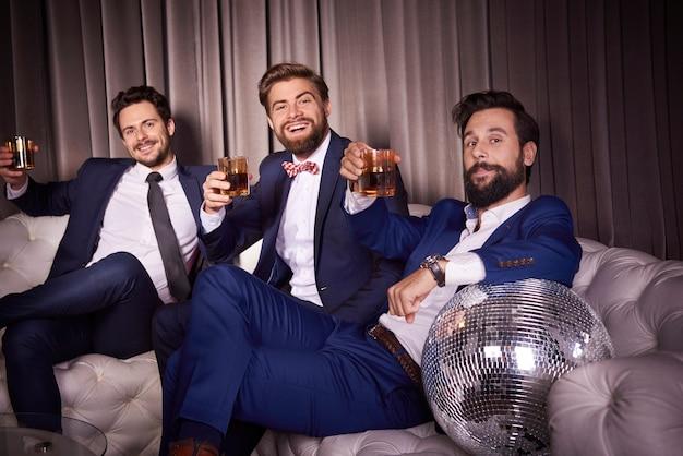 Portret eleganckich mężczyzn z whisky w klubie nocnym