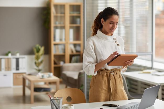 Portret eleganckiej bizneswoman za pomocą cyfrowego tabletu z bezprzewodowymi słuchawkami, stojąc przy biurku w biurze lub w domu, kopia przestrzeń