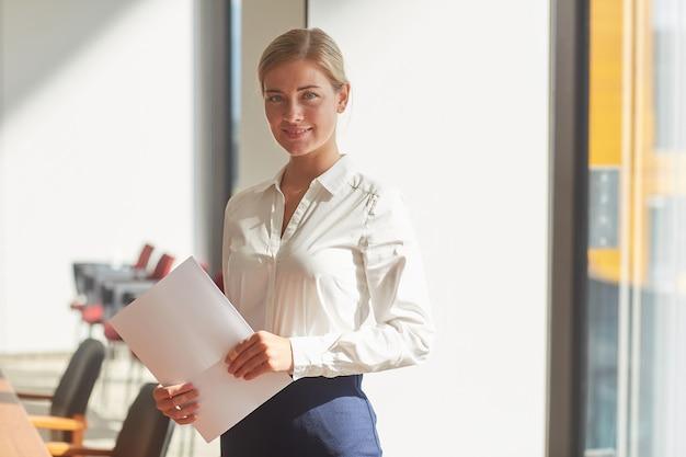 Portret eleganckiej blond bizneswoman noszenia talii przy koszuli stojącej przy oknie w biurze w słońcu