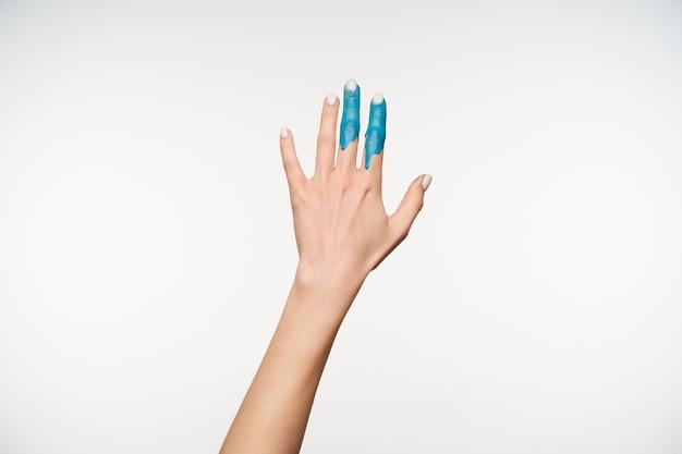 Portret eleganckiej kobiety podniesionej dłoni z niebieską farbą na palcu wskazującym i środkowym palcu, ciągnąc go do przodu, będąc na białym tle
