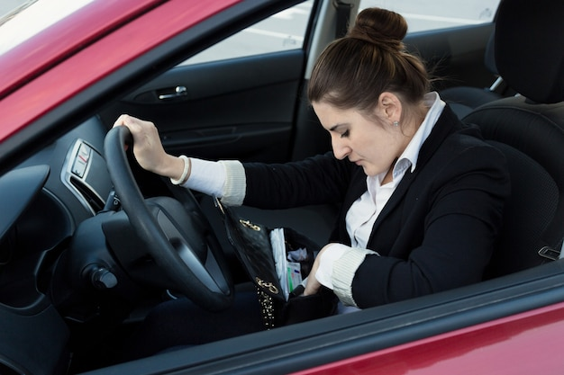 Portret eleganckiej kobiety prowadzącej samochód i zaglądającej do torebki