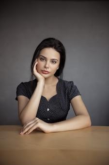 Portret eleganckiej kobiety siedzącej w pomieszczeniu