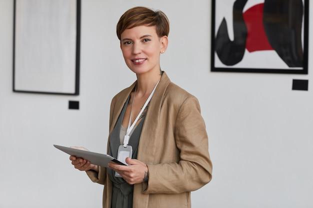 Portret eleganckiej, kreatywnej kobiety w pasie, uśmiechającej się do kamery i trzymającej cyfrowy tablet podczas planowania wystawy w galerii sztuki,