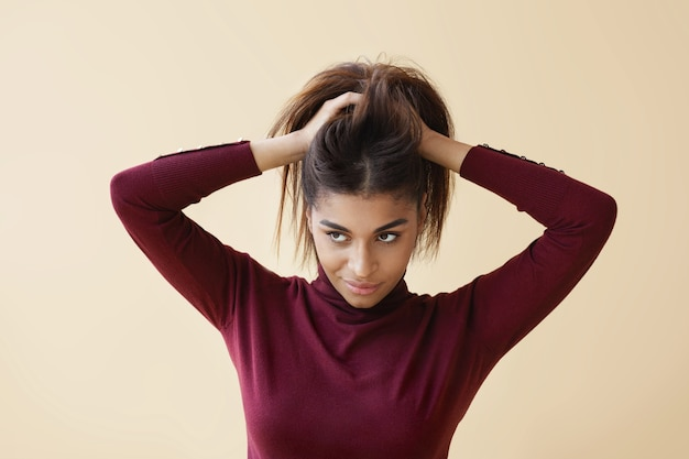 Portret eleganckiej młodej afro amerykanki w modnym swetrze z golfem, odwracającej wzrok z tajemniczym uśmiechem, jakby miała świetny pomysł podczas układania włosów, przygotowując się rano do pracy