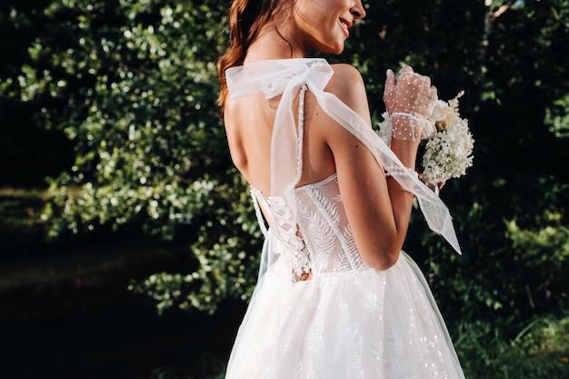 Portret eleganckiej panny młodej w białej sukni z bukietem w przyrodzie w parku przyrody.model w sukni ślubnej i rękawiczkach oraz z bukietem.białoruś