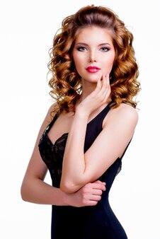 Portret eleganckiej pięknej kobiety w czarnej sukni ręką w pobliżu twarzy - na białym tle na białym tle.