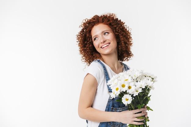 Portret eleganckiej rudowłosej kręconej kobiety 20s w dżinsowym kombinezonie, uśmiechniętej i trzymającej bukiet kwiatów odizolowanej na białej ścianie