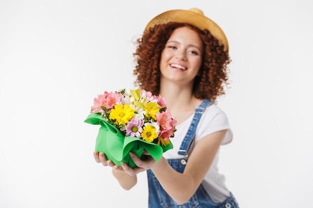 Portret eleganckiej rudowłosej kręconej kobiety w wieku 20 lat w letnim słomkowym kapeluszu uśmiecha się i trzyma pudełko na kwiaty izolowane nad białą ścianą