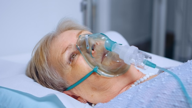 Portret emerytowanej starszej kobiety oddychającej powoli z maską tlenową podczas epidemii koronawirusa covid-19. chora starsza pani leżąca w szpitalnym łóżku, leczona na śmiertelną infekcję
