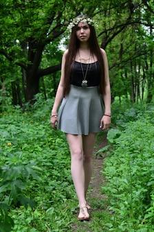 Portret emocjonalna młoda dziewczyna z kwiecistym wiankiem na jej głowie i błyszczącymi ornamentami na jej czole. śliczna brunetka pozuje w pączkującym pięknym lesie w dniu na świetnym dniu
