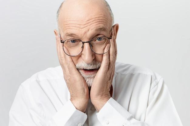 Portret emocjonalnego zdesperowanego starszego mężczyzny z brodą i łysą głową, trzymającego się za ręce na twarzy, wpadającego w panikę, ponieważ zapomniał wziąć lekarstwa, mając sfrustrowany przerażony wyraz twarzy